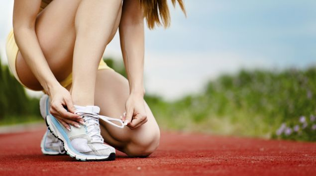 Man sieht eine Läuferin, die ihre Laufschuhe schnürt.