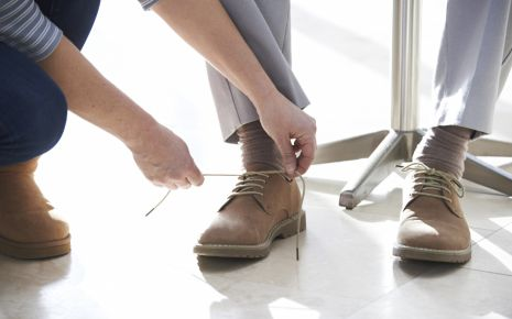 Eine Frau bindet einem Mann die Schuhe zu.