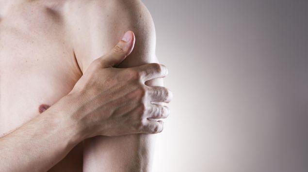 Ein Mann hält mit der rechten Hand seinen linken Arm unterhalb der Schulter.