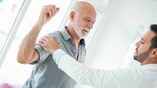 Ein Arzt untersucht die Schulter eines älteren Mannes.