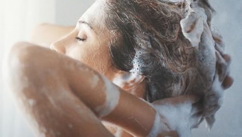 Eine Frau wäscht sich die Haare.