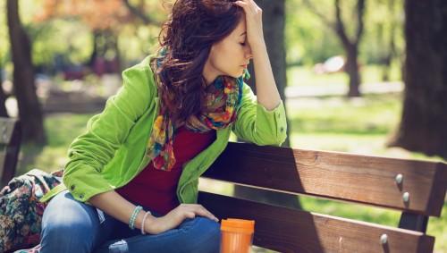 Das Bild zeigt eine Frau, die mit typischen Symptomen eines Schwächeanfalls auf einer Parkbank sitzt.