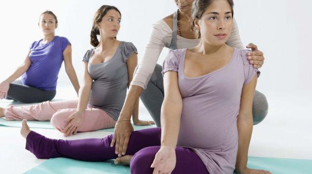 Drei Schwangere dehen sich, unterstützt von einer Hebamme.