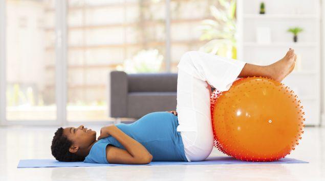 Schwangere liegt auf dem Rücken, die Füße auf einem Gymnastikball.