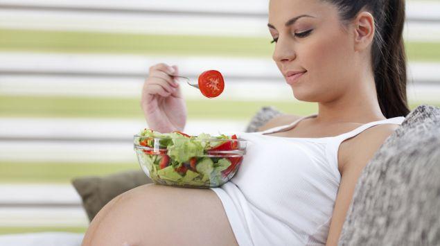 Schwangere isst Salat.