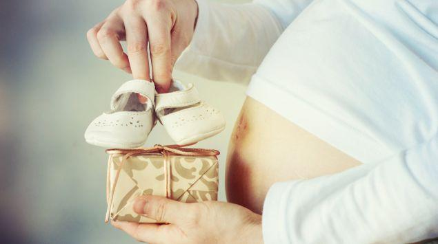 Das Bild zeigt eine Schwangere mit einem Paar Babyschuhen in der Hand.