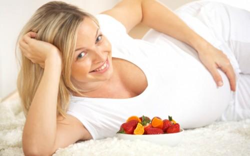 Eine Schwangere hält sich den Bauch.