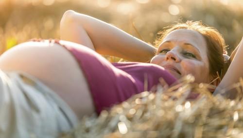 Eine Schwangere liegt auf einem Feld.