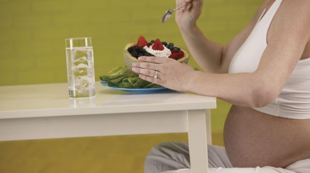 Schwangere isst ein Dessert.