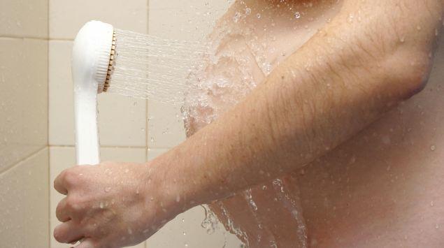 Eine Schwangere duscht ihren Bauch.