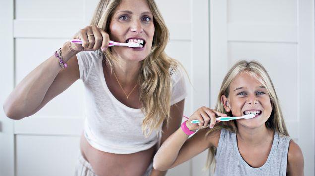 Schwangere und Mädchen putzen Zähne.