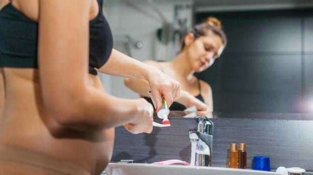 Eine schwangere Frau putzt ihre Zähne.