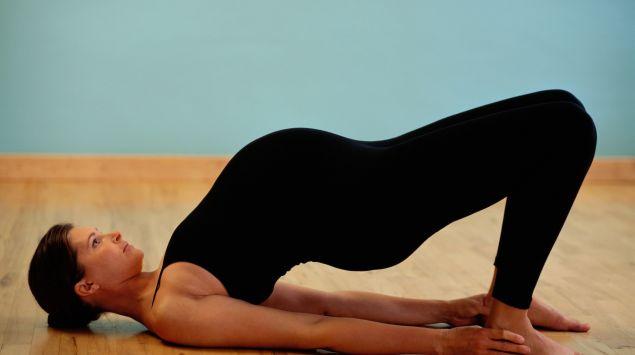 Schwangere in Rückenlage dehnt den Rücken.