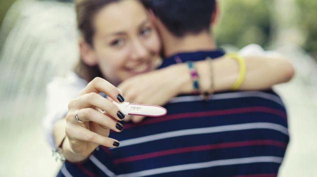 Das Bild zeigt ein glückliches Paar mit einem Schwangerschaftstest in der Hand.