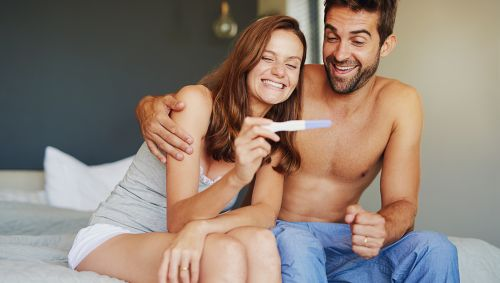 Junges Paar freut sich über positiven Schwangerschaftstest.