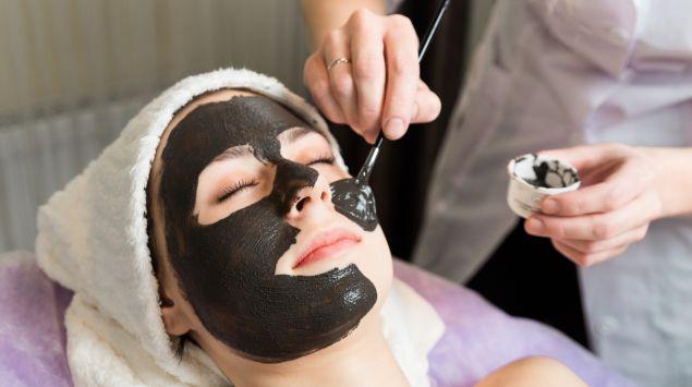 Eine Frau lässt sich eine schwarze Maske auftragen.