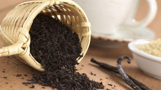 Aus einem umgekippten Körbchen fällt schwarzer Tee auf einen Tisch.