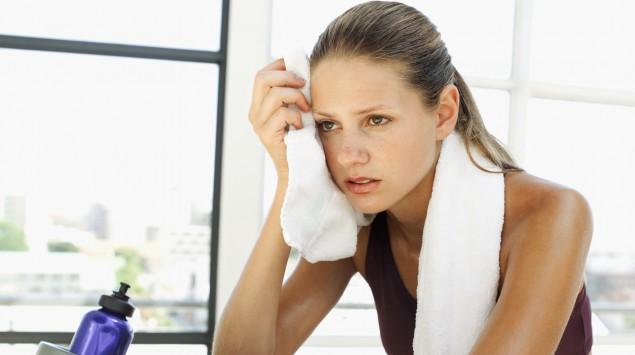 Das Bild zeigt eine schwitzende Frau mit einem Handtuch auf einem Fitnessgerät.