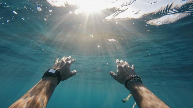 Man sieht einen Menschen beim Brustschwimmen im Wasser.