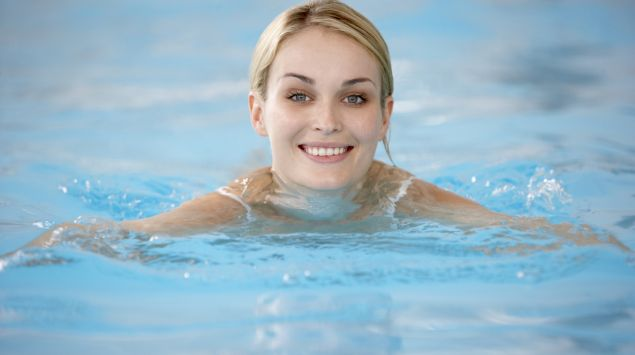 Eine junge Frau schwimmt in einem Schwimmbecken.