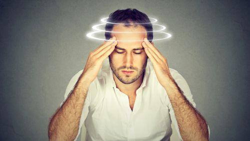 Junger Mann fasst sich an die Schläfen, Kreise um den Kopf verdeutlichen die Kreislaufprobleme