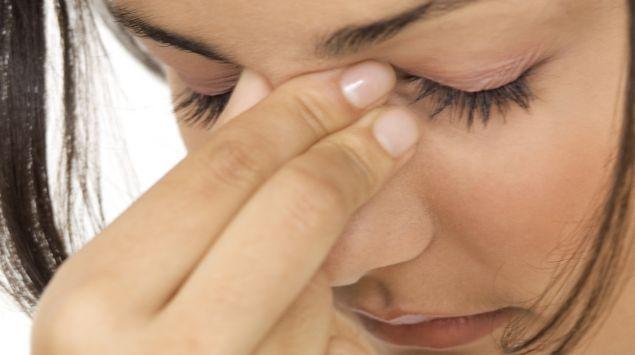 Eine Frau fasst sich an die Nasenwurzel.