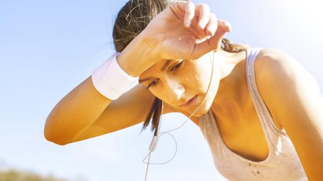 Eine junge Frau im Trainingsoutfit wischt sich den Schweiß von der Stirn.
