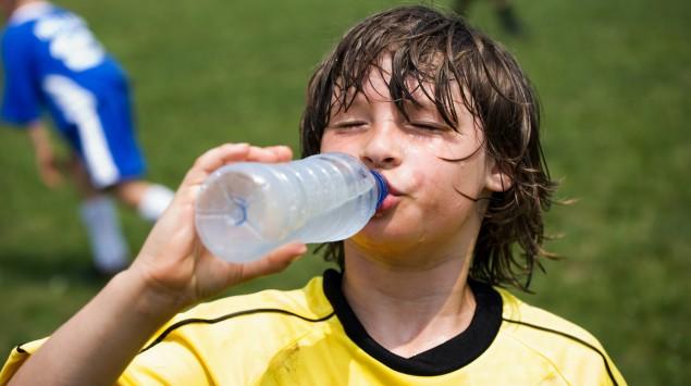 Verschwitzter Junge trinkt beim Fußballspiel Wasser.