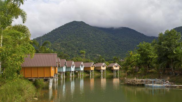 Man sieht einen See in den Tropen mit Häusern auf Stelzen.