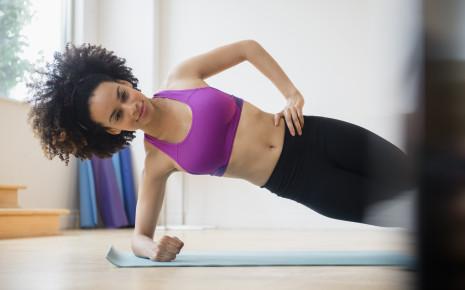 Eine Frau macht eine Fitnessübung (seitlicher Plank).