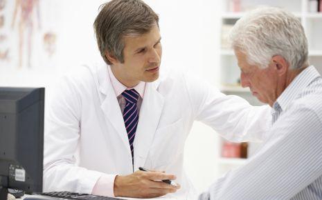 Ein Arzt im Gespräch mit einem älteren Mann.