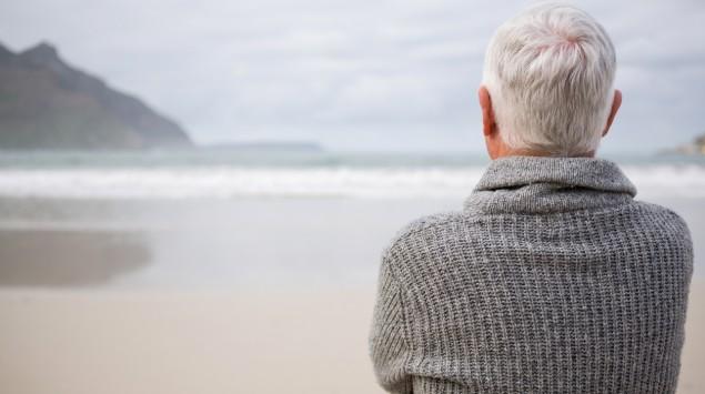 Ein älterer Mann steht am Strand und schaut aufs Meer.