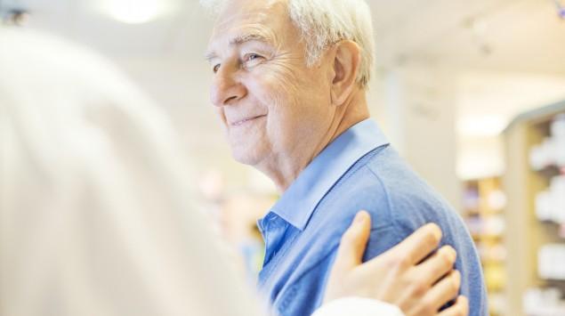 Jemand legt einem Senioren tröstend die Hand auf die Schulter.