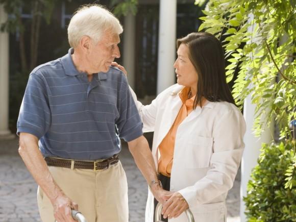 Das Bild zeigt einen älteren Mann mit einem Rollator, der sich mit einer Ärztin unterhält.