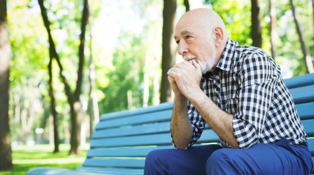 Ein älterer Mann sitzt in einem Park auf einer Bank.