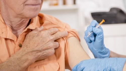 Ein älterer Mann erhält eine Impfinjektion in den Oberarm.
