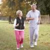 Ein älteres Paar joggt in herbstlicher Umgebung.