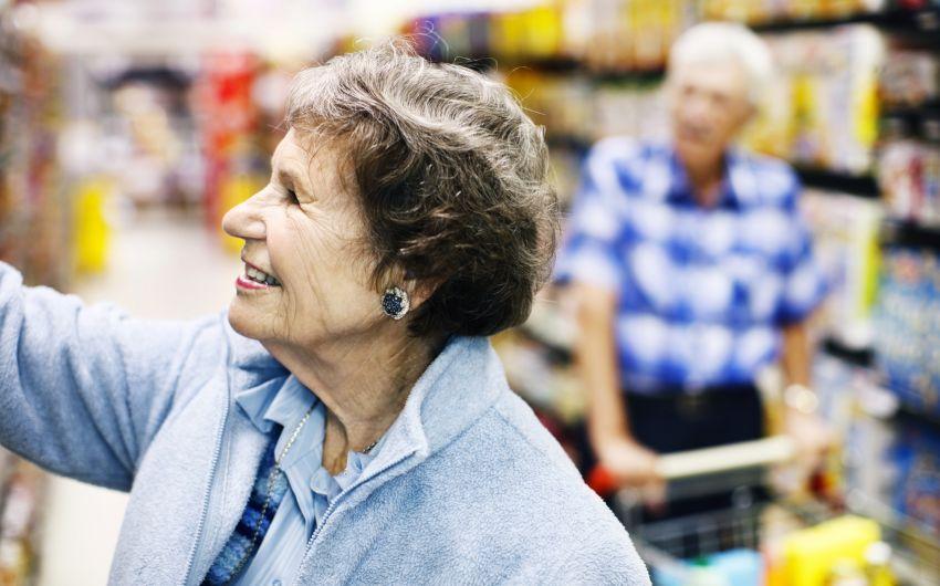 Vitamin D: Eine ältere Frau greift im Supermarkt nach einer Ware im Regal.