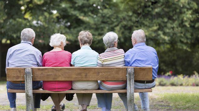 Auf einer Bank sitzt eine Gruppe Senioren.