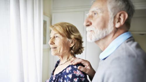 Ein älteres Paar schaut aus dem Fenster.