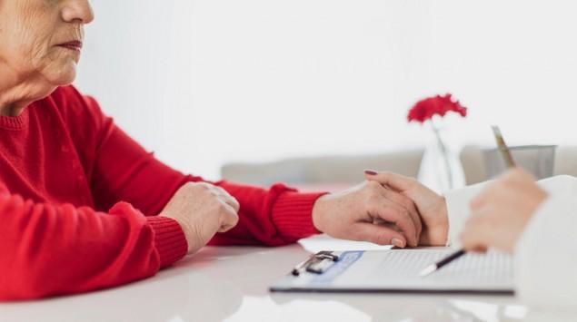 Ein Arzt hält einer Seniorin die Hand.