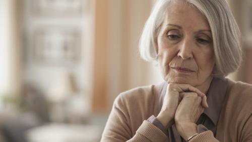 Eine ältere Frau mit sorgenvollem Blick.