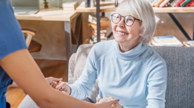 Eine Physiotherapeutin hilft einer Seniorin beim Aufstehen.