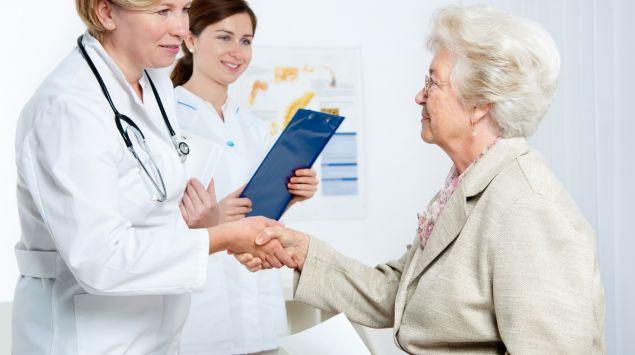 Eine Ärztin begrüßt eine ältere Patientin in der Praxis.