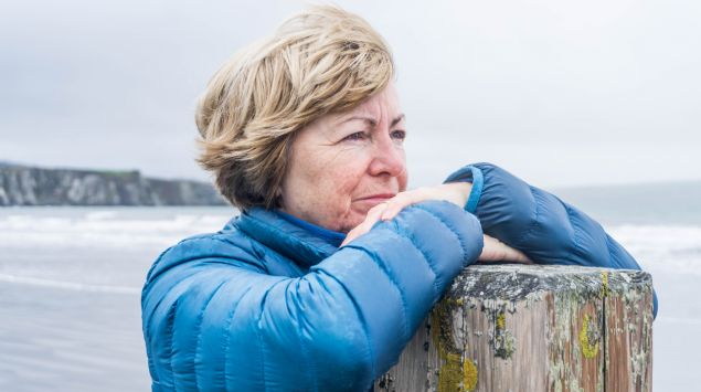 Eine ältere Frau am Meer lehnt sich an einen Holzpfosten und blickt in die Ferne.