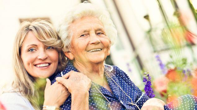 Das Bild zeigt eine ältere Frau, die die Hand einer jüngeren hält.