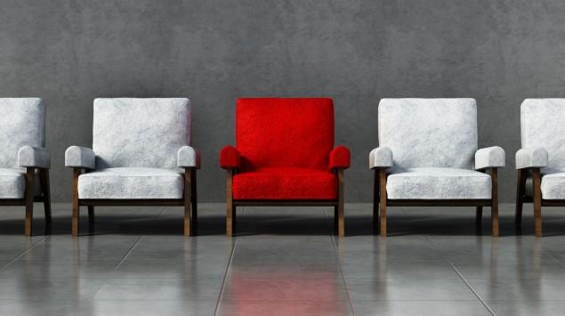 Mehrere Sessel nebeneinander, einer davon ist rot