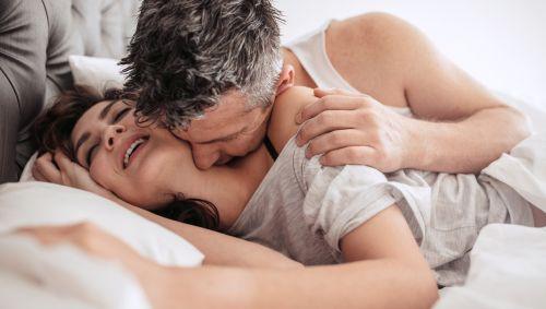 Ein Mann küsst eine Frau auf den Hals.