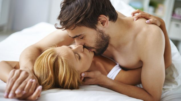 Das Bild zeigt ein Paar im Bett, das sich küsst.
