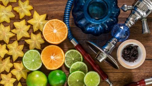 Auf einem Holztisch liegen verschiedene Teile einer Shisha, mehrere Sternfrüchte sowie verschiedene Zitrusfrüchte.